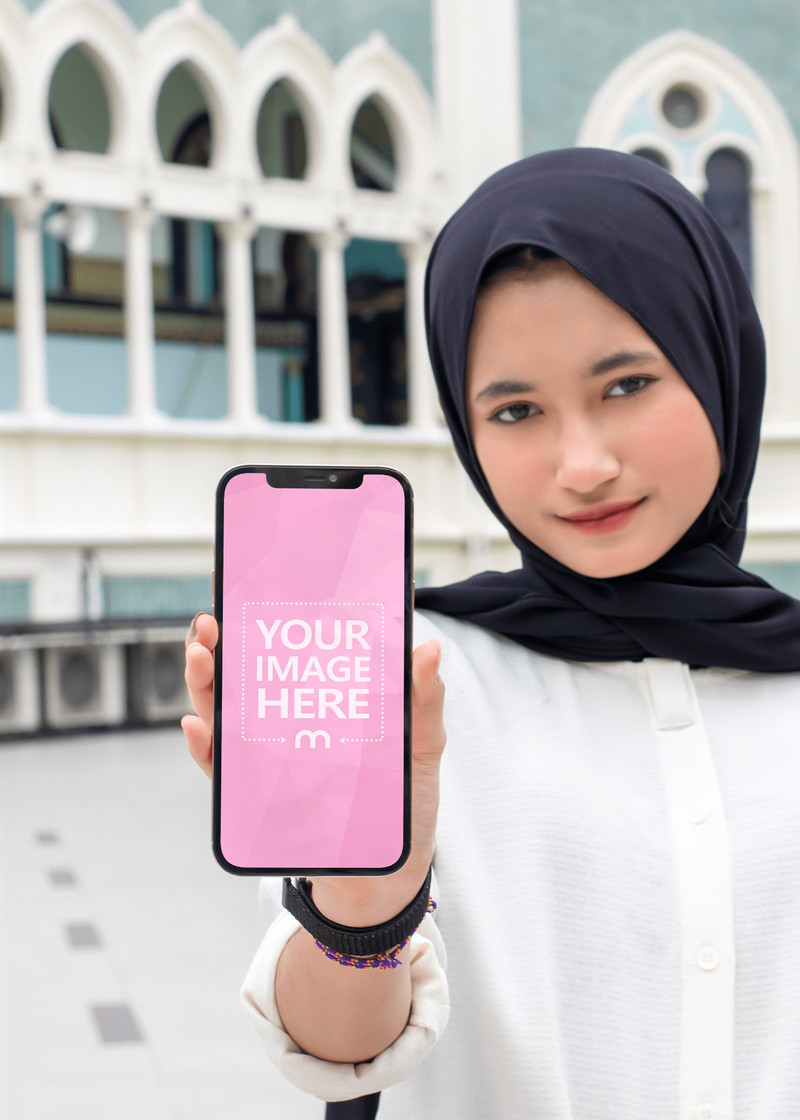 iPhone Mockup With a Young Muslim Woman Holding on it One Hand