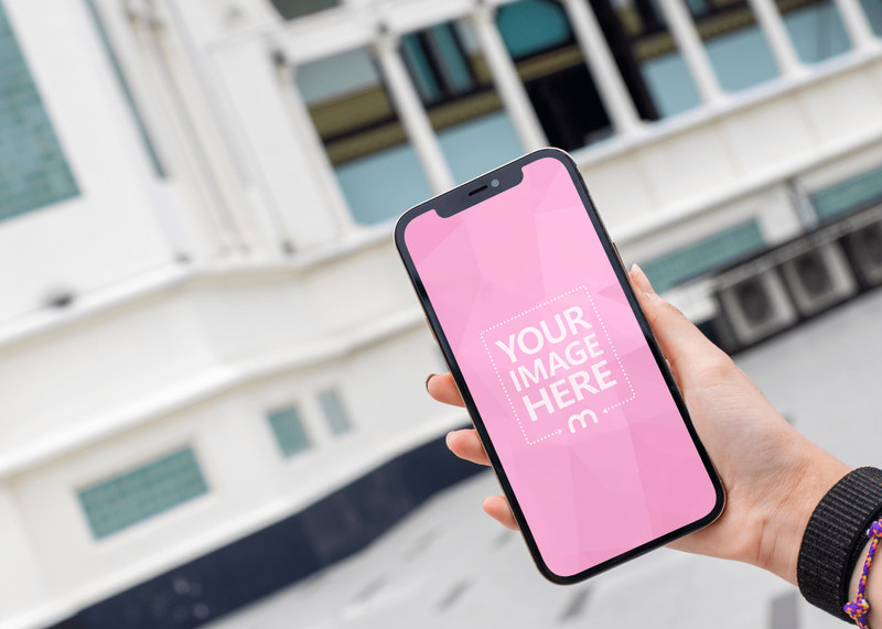 Mockup of an iPhone Featuring a Hand Holding it While Showing a Mosque