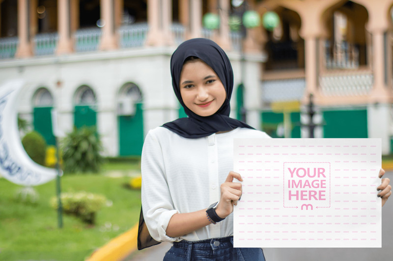 Mockup of an A3 Paper Featuring a Smiling Muslim Woman Holding it