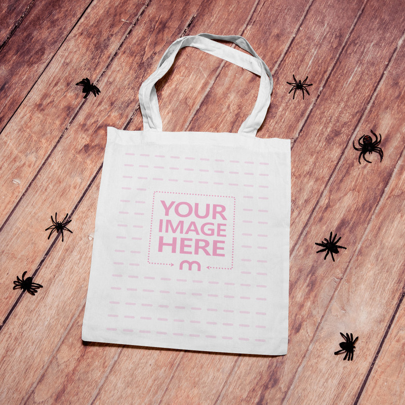 Halloween Mockup of a Tote Bag on top of a Wooden Flooring With Spiders