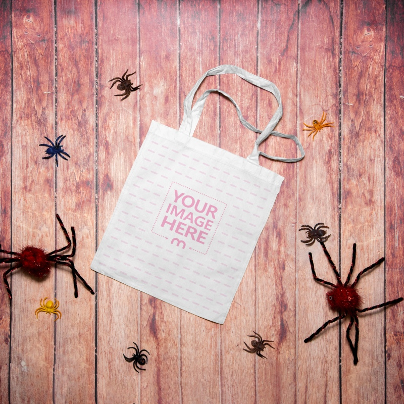 Halloween Tote Bag Mockup With the Bag Surrounded by Colored Spiders